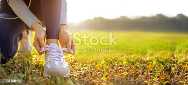 istock young woman runner tying her shoes preparing for a jog outside at morning 1298108434