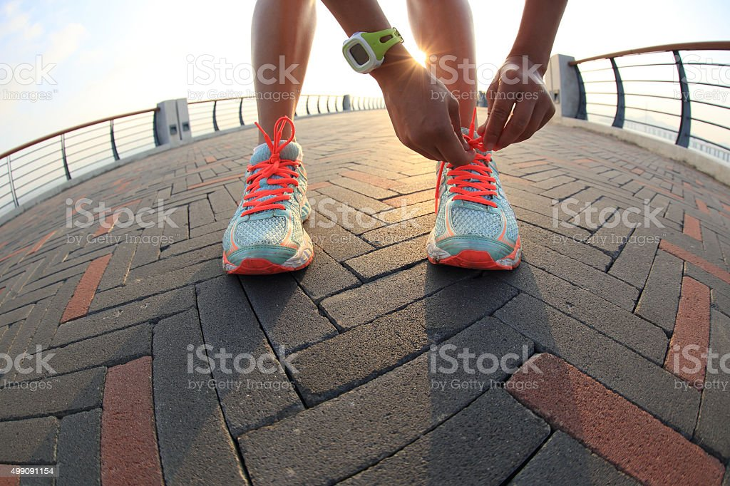 young woman runner tying shoelace  at the sunrise seaside stock photo
