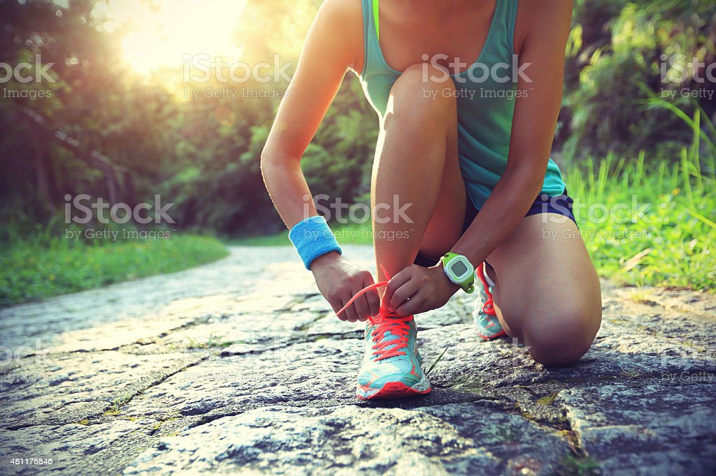 young woman runner tying shoelaces on stone trail stock photo