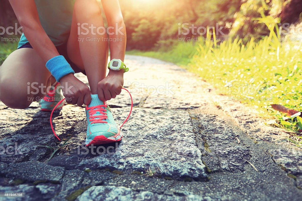 young woman runner tying shoelaces on stone trail young woman runner tying shoelaces on stone trail 2015 Stock Photo