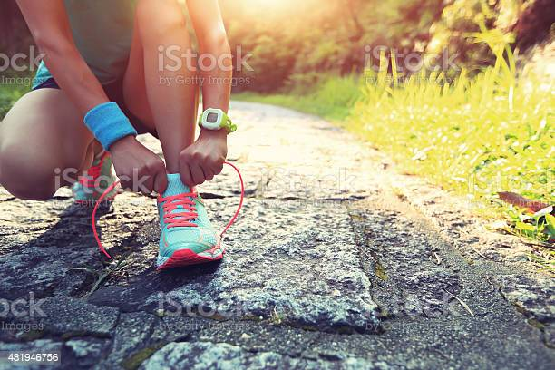 Young Woman Runner Tying Shoelaces On Stone Trail Stock Photo - Download Image Now