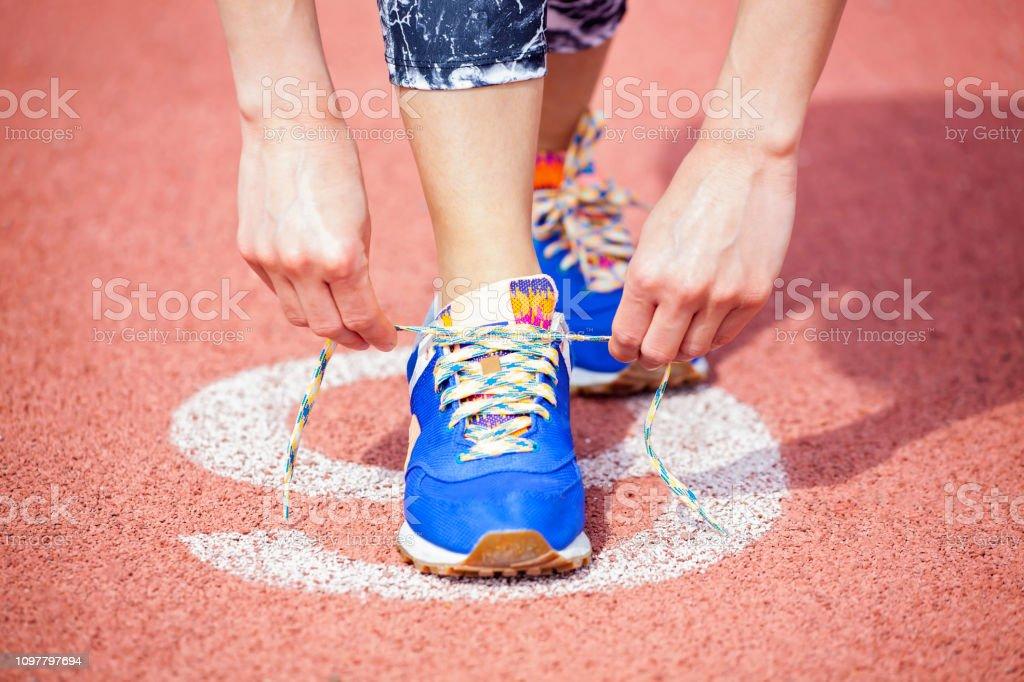 Genç kadın atlet ayakkabı bağcığı bağlama stok fotoğrafı