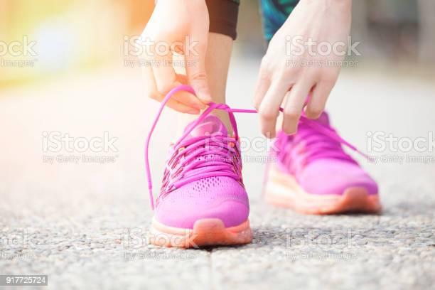 Young woman runner tying shoelaces picture id917725724?b=1&k=6&m=917725724&s=612x612&h=iudbiu4kpephrdj rlbid mlpciratoz719p79soknc=