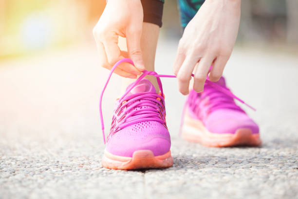 Young woman runner tying shoelaces stock photo