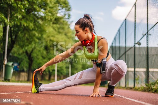 520047182istockphoto Young woman runner warm up outdoor and streching 969627824