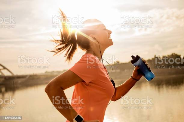 Photo of Young woman running against morning sun