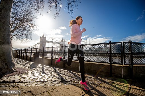 Young woman in sports clothes running alone down the walkway by the river Thames at time of Covid-19 isolation