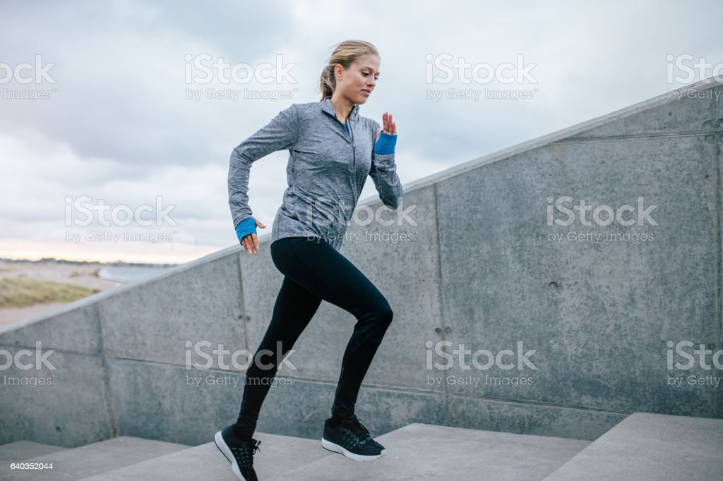 Young woman running alone up stairs stock photo
