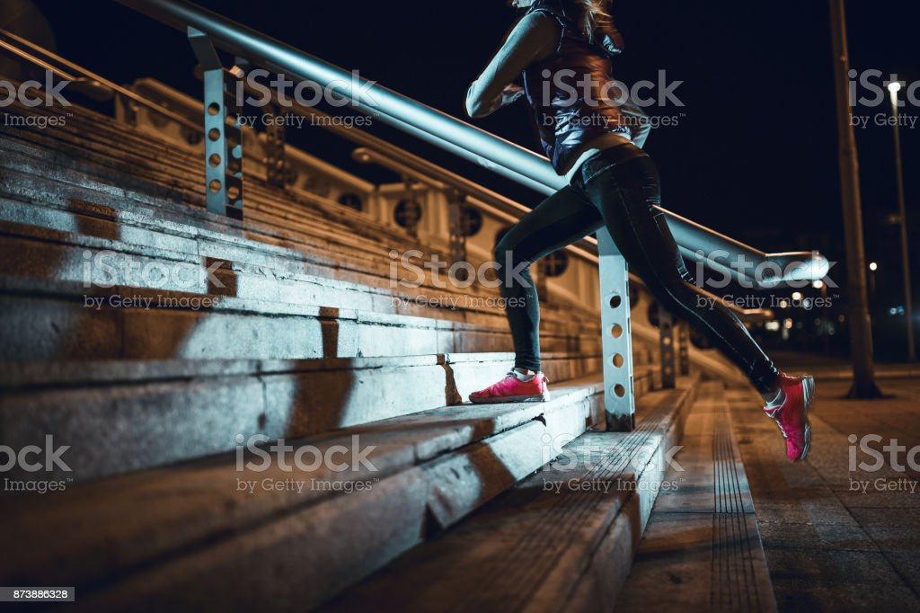 Young woman running at night in a urban city area stock photo
