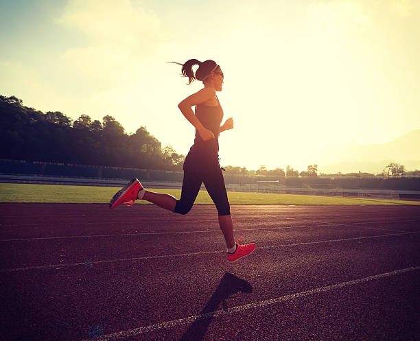 Young woman running during sunny morning on stadium track - foto de stock
