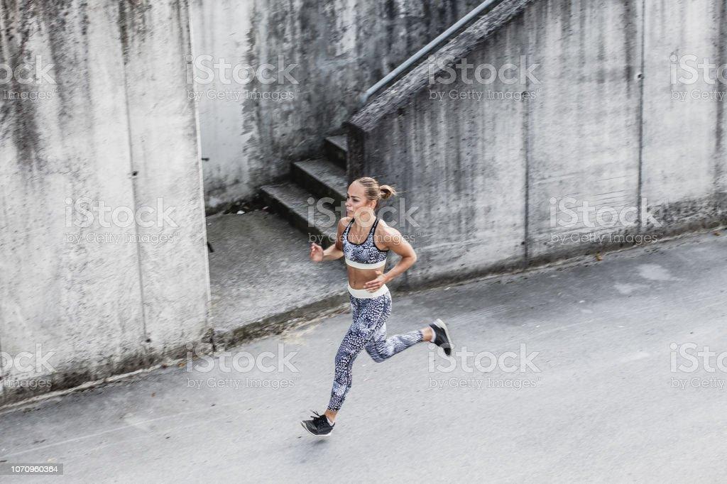 Junge Frau läuft in einem städtischen Umfeld – Foto