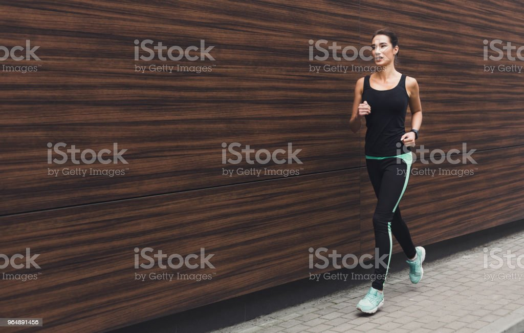 Young woman running in city copy space royalty-free stock photo