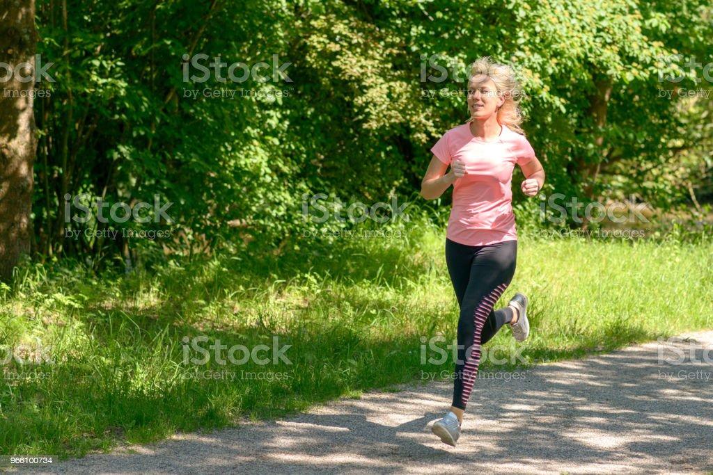 Junge Frau im Land laufen - Lizenzfrei Aktiver Lebensstil Stock-Foto