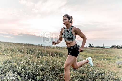 Young female athlete in sports clothing running in nature on grass field