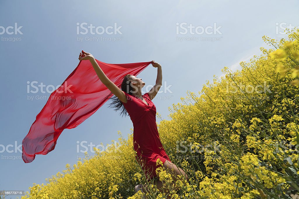 Young woman running in rape holding red scarf to wind stock photo