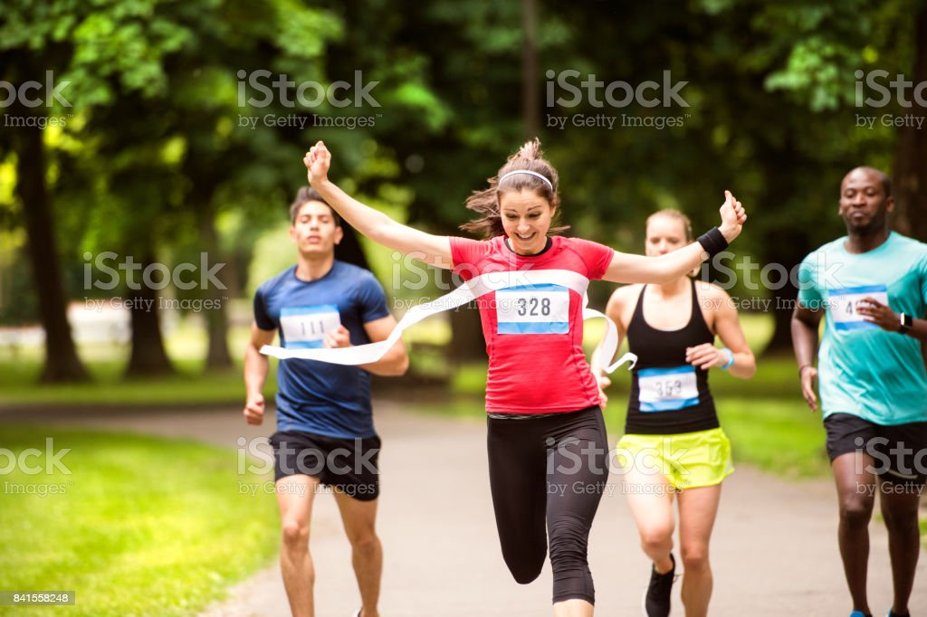 Young woman running in the crowd crossing the finish line. stock photo