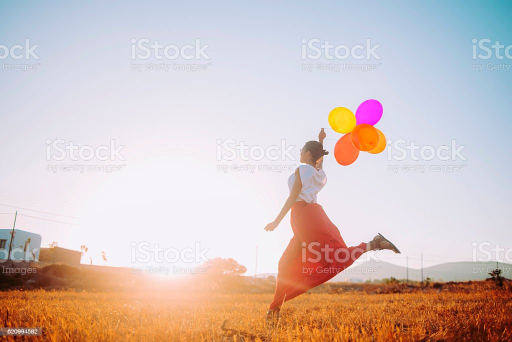 young woman running in the field holding colorful balloons stock photo