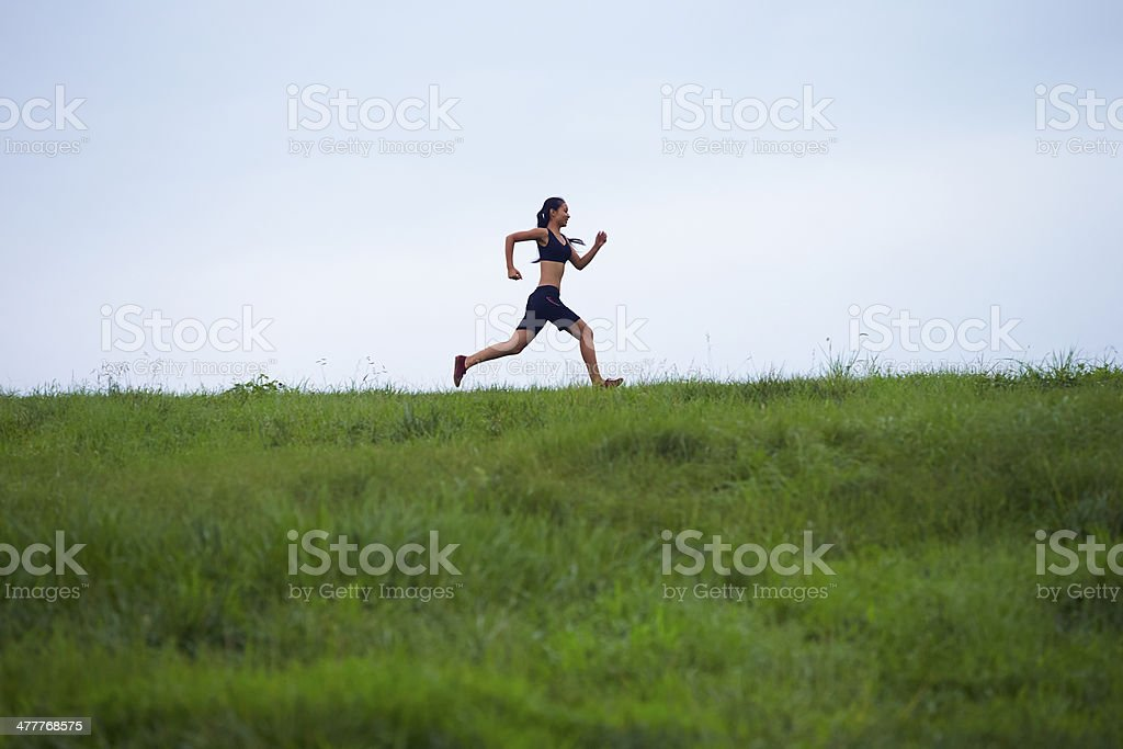 young woman running in the field royalty-free stock photo