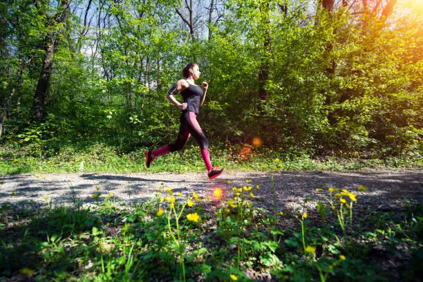 eine junge frau, die im waldfußweg lief. - joggerin stock-fotos und bilder
