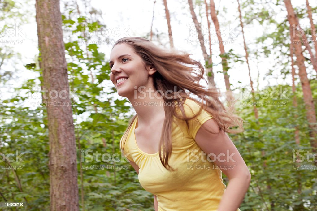 Young woman running in the forest royalty-free stock photo