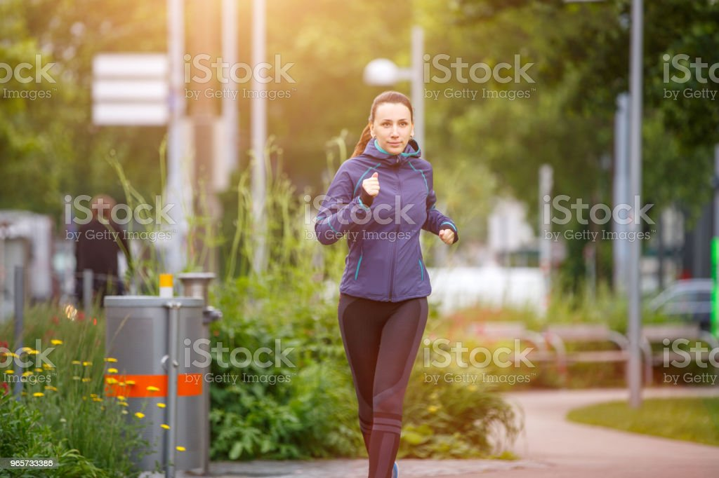 Young woman running in the morning in city park - Royalty-free Adult Stock Photo