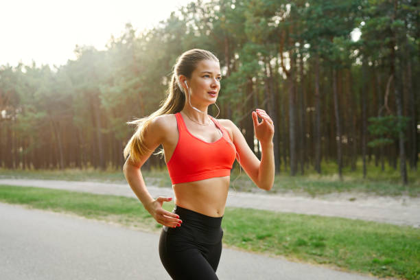 Young woman running in the park A young woman wearing gym clothes running along a park trail while listening to music on headphones women's track stock pictures, royalty-free photos & images