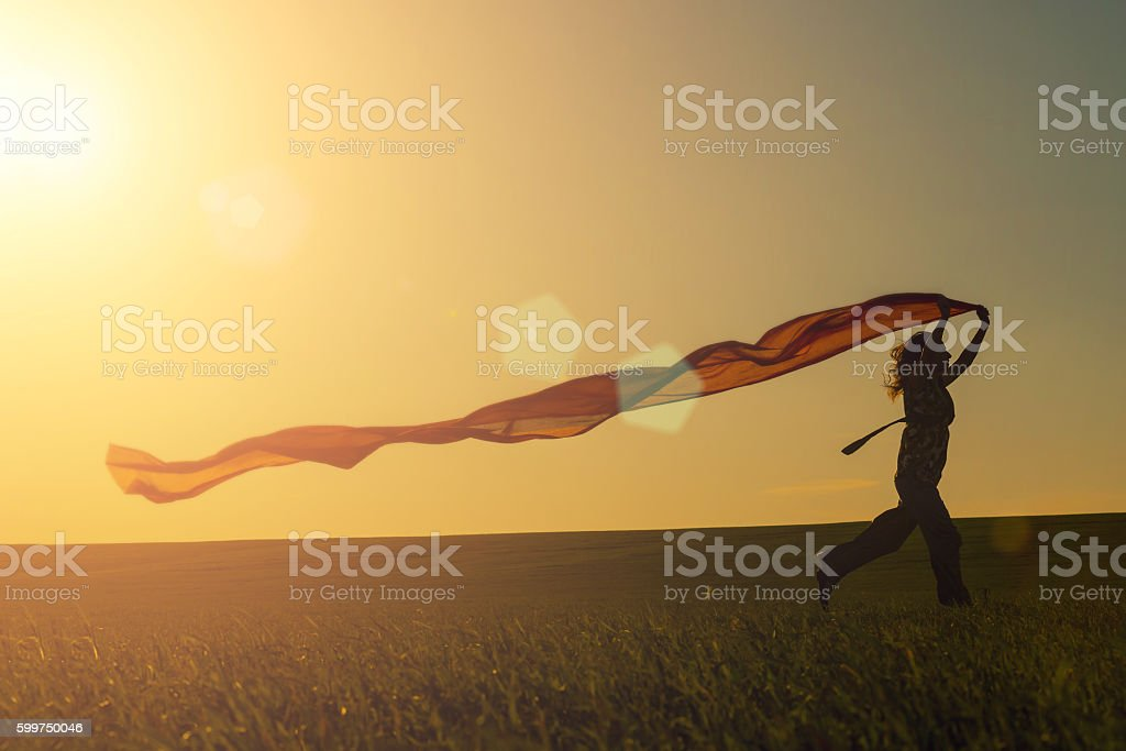 Young woman running on a rural road at sunset in stock photo