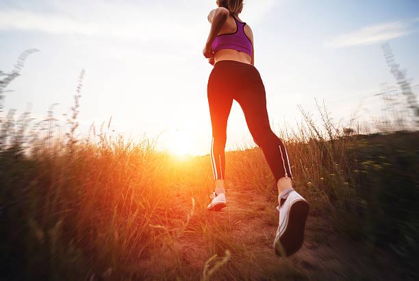 young woman running on a rural road at sunset - jogging hill bildbanksfoton och bilder