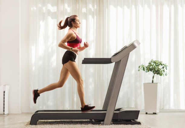 Young woman running on a treadmill at home Full length profile shot of a young woman running on a treadmill at home exercise machine stock pictures, royalty-free photos & images