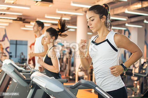 istock Young woman running on a treadmill at the gym. 598549984