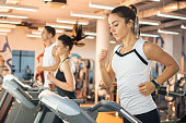 Young woman running on a treadmill at the gym.