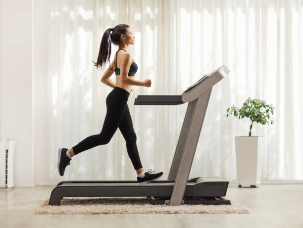 Young woman running on a treadmill indoors Full length profile shot of a young woman running on a treadmill indoors treadmill stock pictures, royalty-free photos & images
