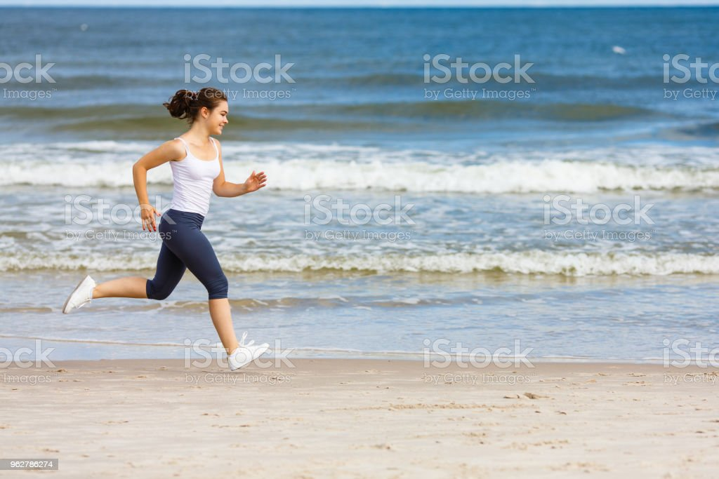 Young woman running on beach - Foto stock royalty-free di Acqua