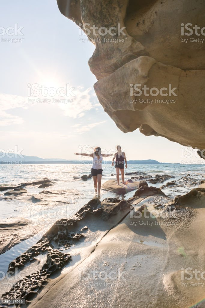 Young Woman Running on Beach with Open Arms, Embracing Nature stock photo