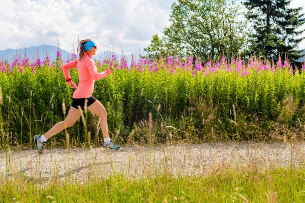 junge frau läuft auf landstraße in bergen, sommertag - joggerin stock-fotos und bilder