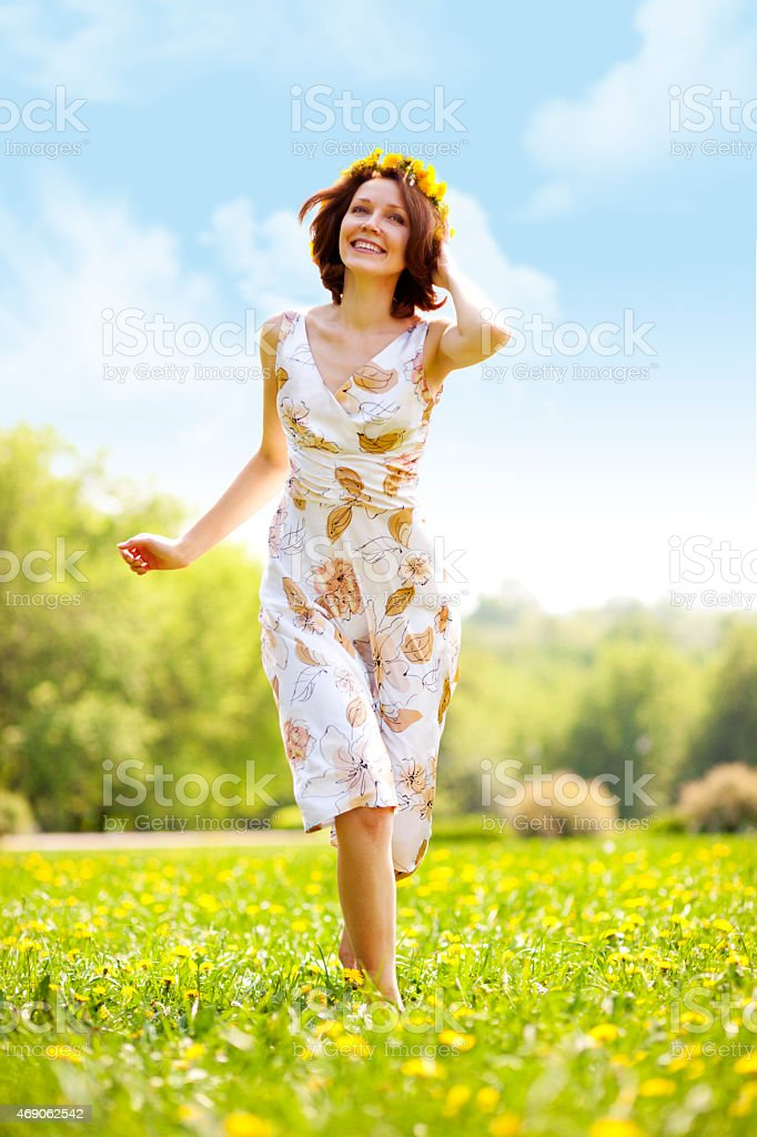 Young woman running on grass stock photo