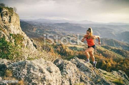 Action photo of athlete woman trail runner running and climbing over mountain cliff. Extreme terrain and beautiful light before sunset after rain.