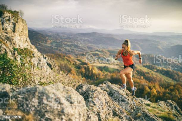 Young woman running on mountain Action photo of athlete woman trail runner running and climbing over mountain cliff. Extreme terrain and beautiful light before sunset after rain. Achievement Stock Photo