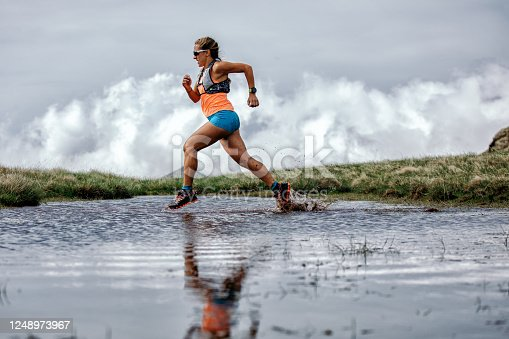 Action photo of athlete woman trail runner running through water on small lake on mountain. She wears sport clothes and west. Dramatic sky after rain.