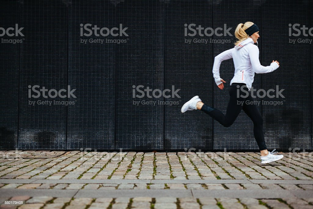 Young woman running on sidewalk in morning stock photo