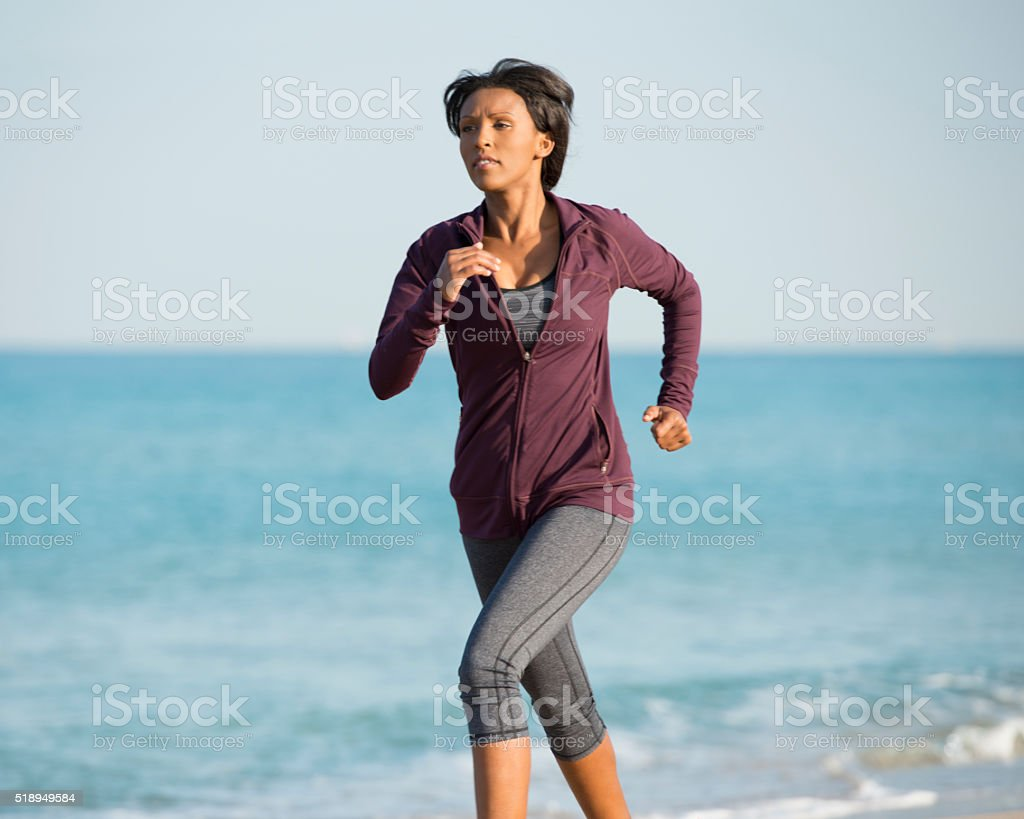 Young woman running on the beach. stock photo