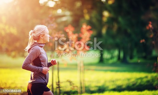 Young woman running in the park. Active person outdoors at the dusk in summer
