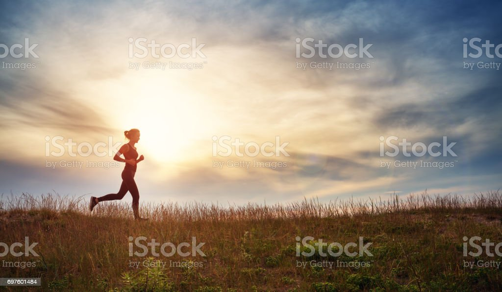 Young woman running on the field near seaside at sunset stock photo