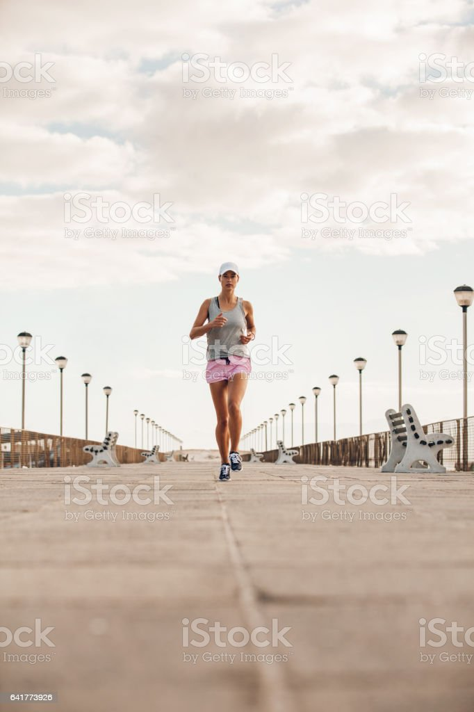 Young woman running on the sea side promenade – Foto