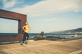 istock Young woman running on wooden sidewalk on a beach 1212395762