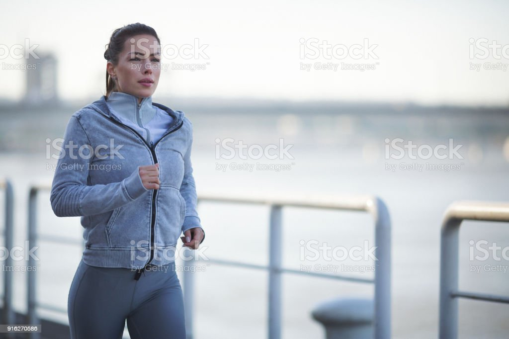 Young woman running outdoors by the river stock photo