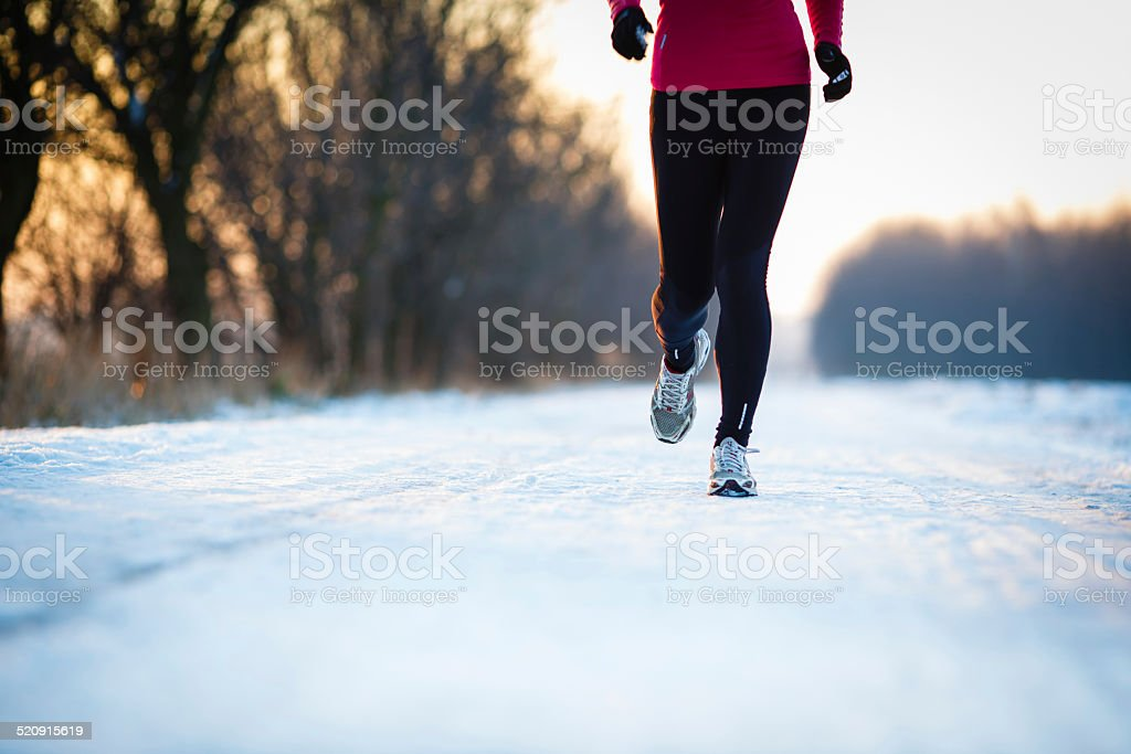 Young woman running outdoors on a cold winter day stock photo