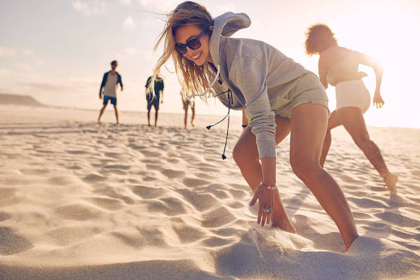 young woman running race with friends at the beach - game of life stock photos and pictures