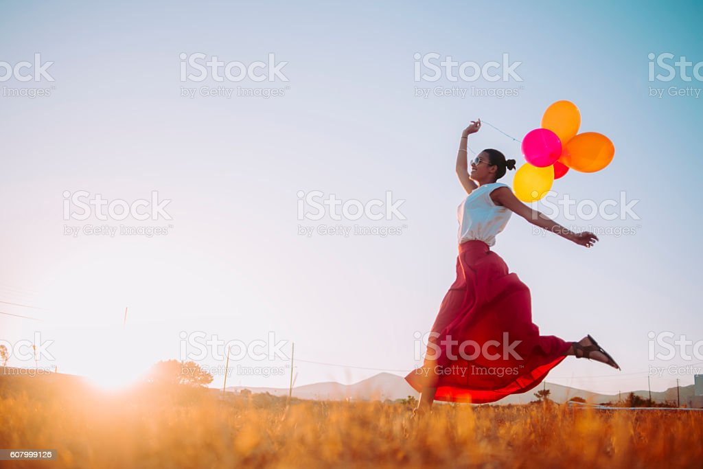 young woman running threw the fields holding balloons stock photo