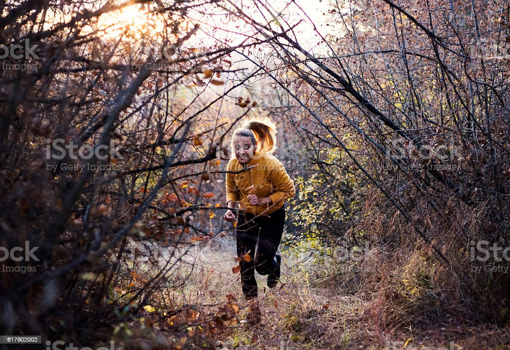 Young woman running through a forest. stock photo